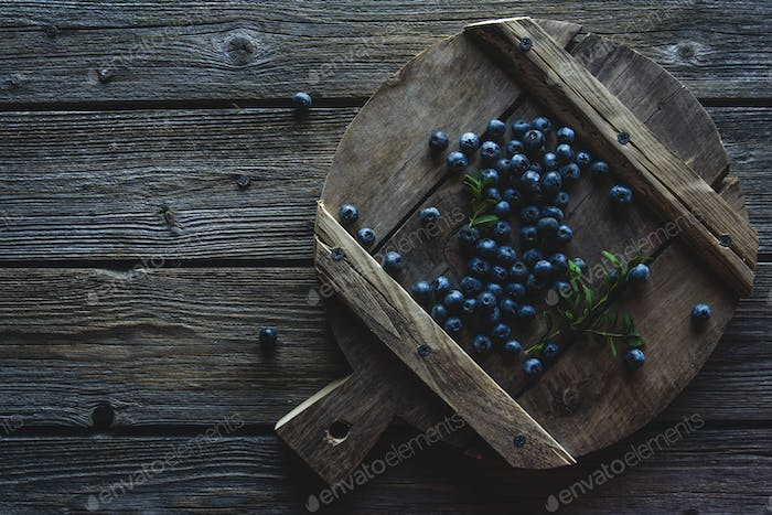 Blueberries on a wood board, wooden background closeup