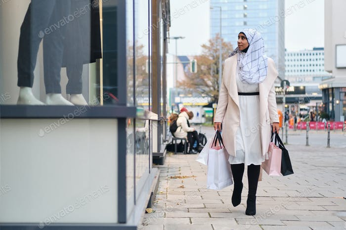 Young stylish Arabic woman in hijab dreamily walking around street with shopping bags