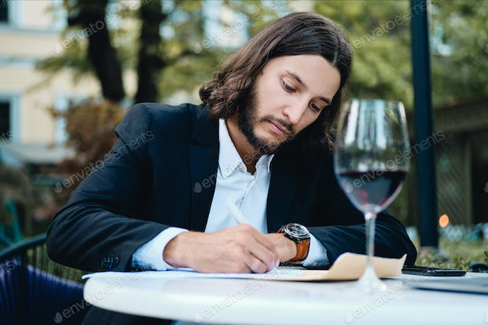 Handsome serious latin businessman with glass of wine thoughtfully working in restaurant outdoor