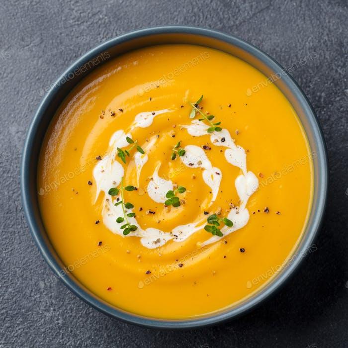 Kürbis, Karottencreme Suppe in einer Schüssel. Schieferhintergrund. Nahaufnahme. Draufsicht.