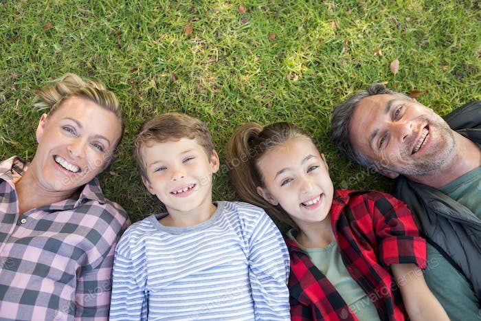 Happy family lying on the grass in park