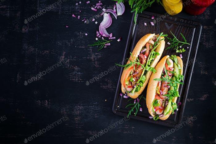 Hot Dog mit Wurst, Gurke, Tomate und roten Zwiebeln