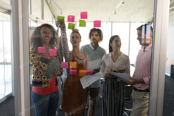 Business colleagues discussing business strategy over sticky notes in modern office