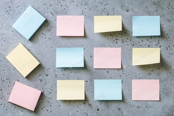 Colorful empty sticky notes on a grey textured background. The concept organization and planning.