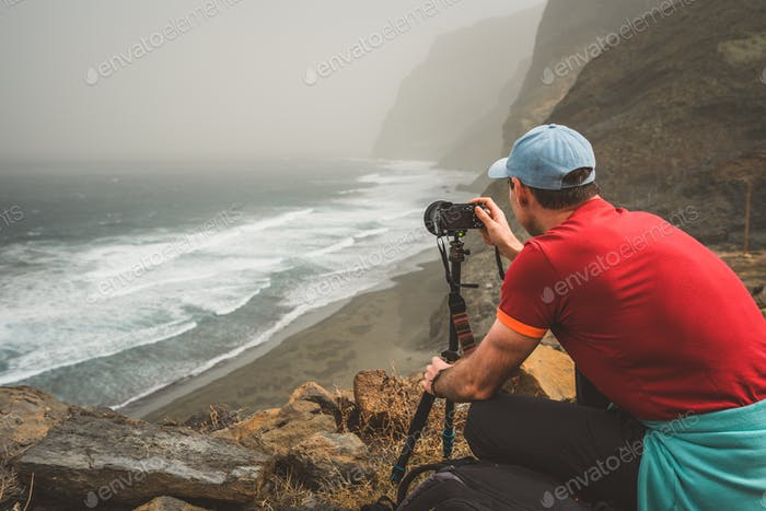 Tourist making photograph of cliff coastline with ocean waves from Cruzinha to Ponta do Sol. Huge