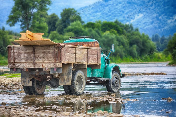 old truck transports cargo wade across the river.