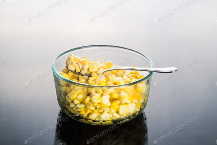 Corn kernels in transparent glass bowl  in dark reflective backg