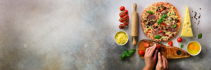 Girl hands making, decopating, preparing pizza with basil leaves on grey light background. Top view