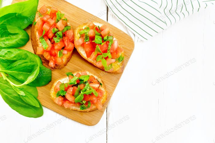 Bruschetta with tomato and spinach on light board top