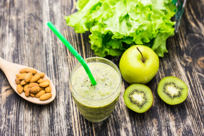 Healthy green smoothie with kiwi and apples on  wooden background