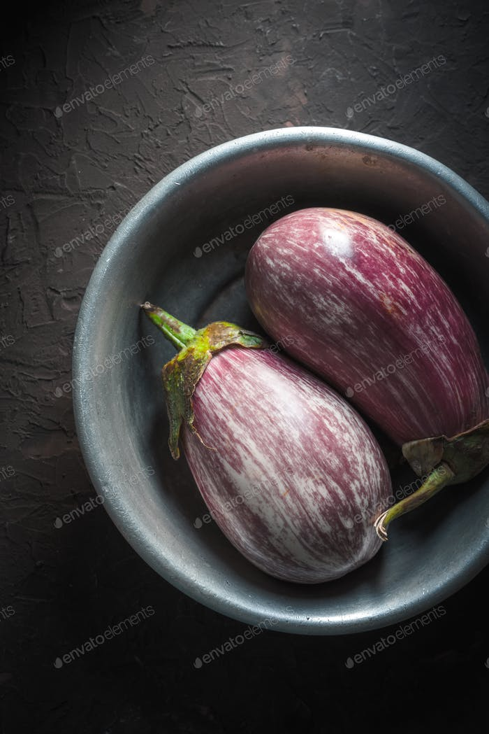 Colored eggplants in a metal bowl on a beige background in the center