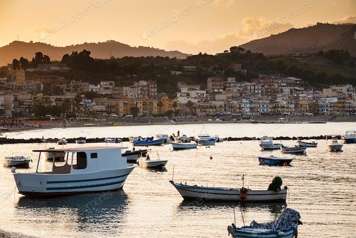 Boote im Yachthafen von Giardini Naxos Stadt bei Sonnenuntergang