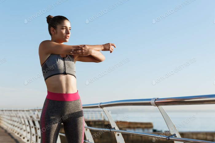 Image of determined female runner stretching on the seaside promenade before jogging. Girl warming