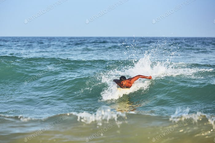 Young man surfing in sea