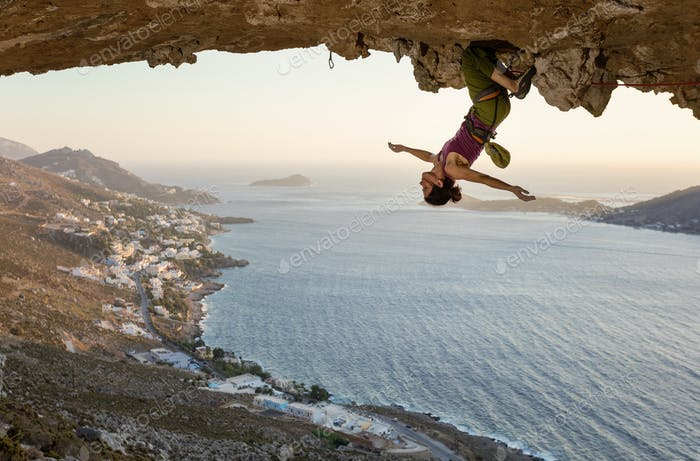 Female rock climber hanging upside down on challenging route
