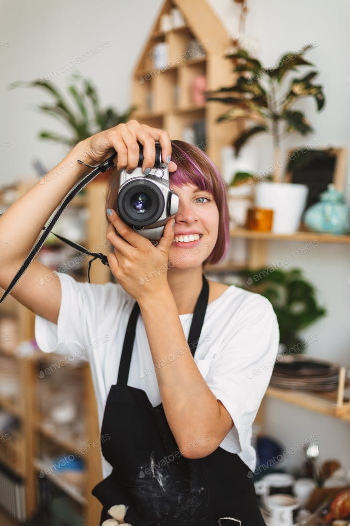 Smiling girl with colorful hair in black apron taking photos on camera