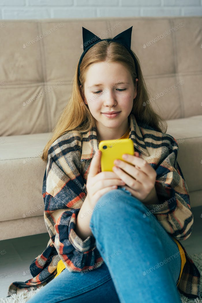 A redhead schoolgirl in cat ears communicates on a mobile phone.