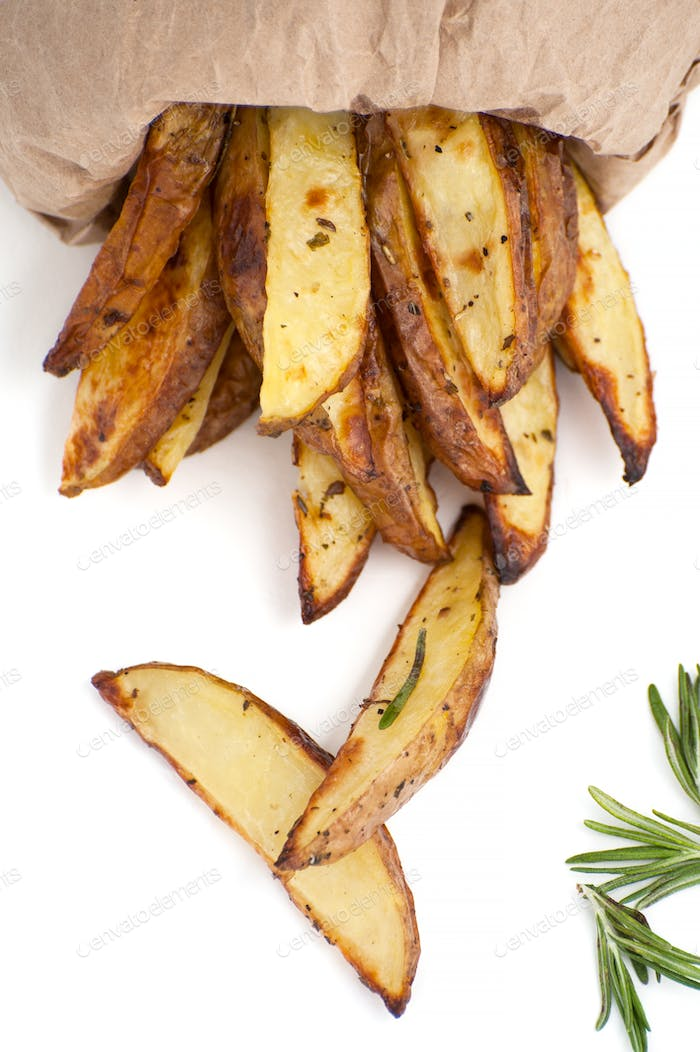 "Slices of baked potato ""rustic"" with rosemary close-up on a whit"