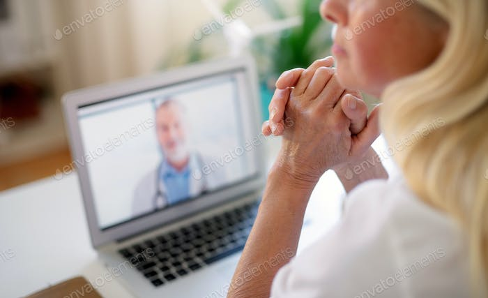 Senior woman with laptop at home, consulting doctor and video call concept