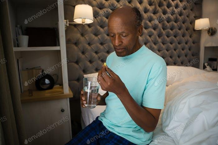 Senior man taking medicine while sitting on bed