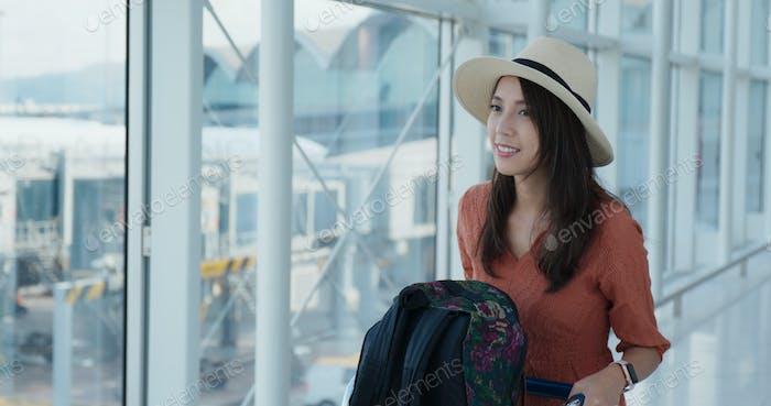 Glückliche Frau wartet auf ihren Flug im Flughafen