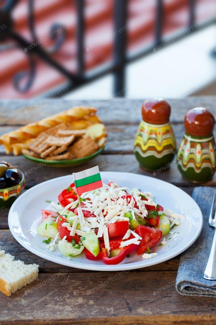 Vegetable Bulgarian Shopska Salad with Bulgaria flag. Wooden background.
