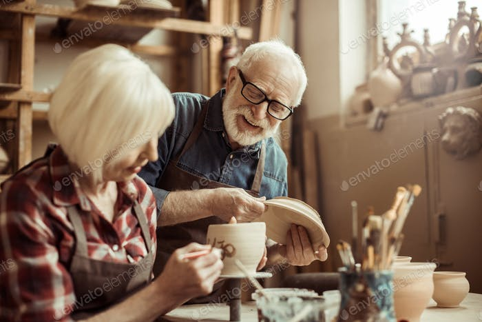 Woman Painting Clay Pot With Senior Potter at Workshop