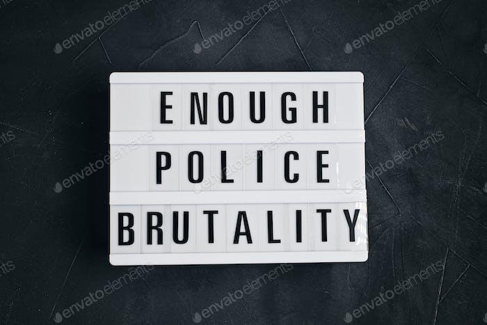 Suficiente texto de brutalidad policial en caja de luz sobre fondo oscuro