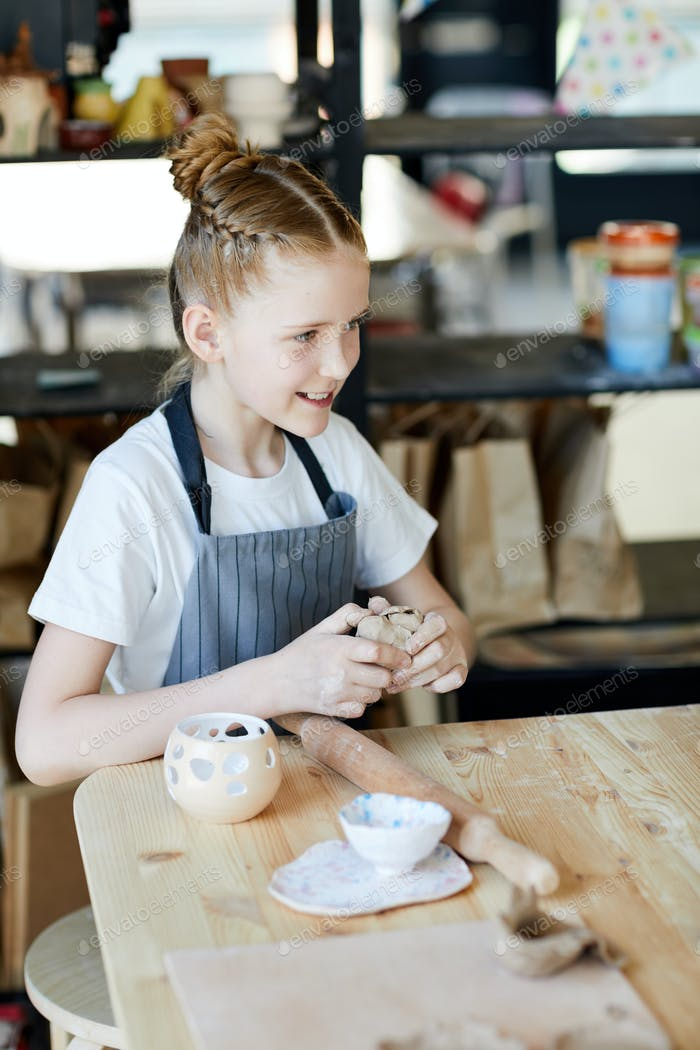 Girl kneading clay