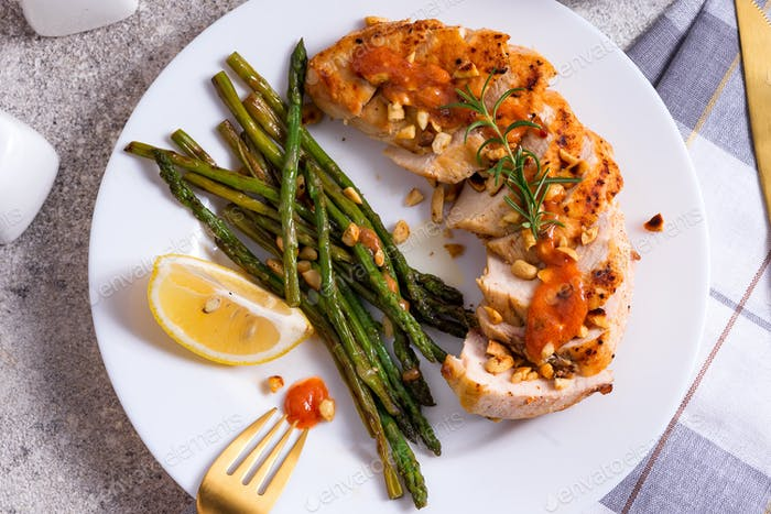 Grilled chicken breast with grilled asparagus and lemon sliceclose-up. Paleo diet. Concept for a