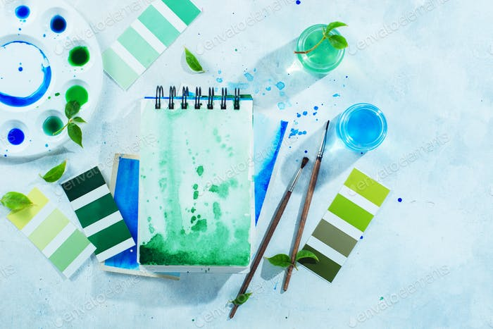 Artist workplace with tools and plants, green and blue watercolor sketchbooks, brushes and color