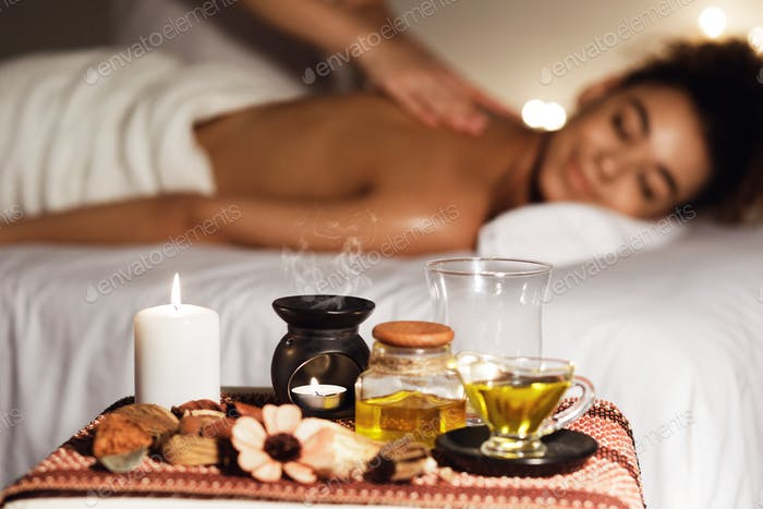 African woman enjoying aromatherapy massage in luxury spa