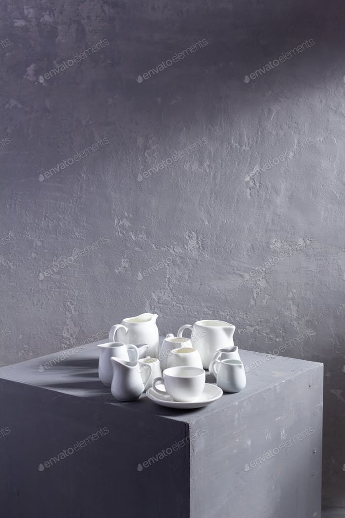Empty crockery or ceramic dishes set. White kitchen dishware and tableware at grey cube