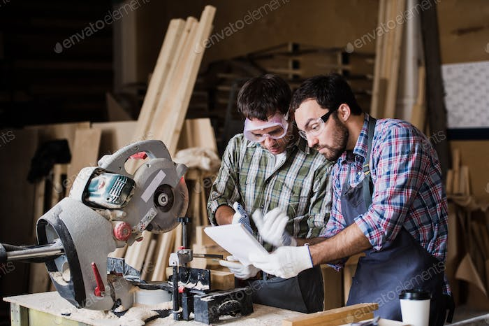 angry boss and worker together in a carpenter's workshop