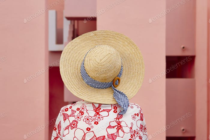 Summer time. Woman with pink geometric building background. Relaxing time