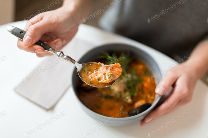 woman eating seafood soup at restaurant
