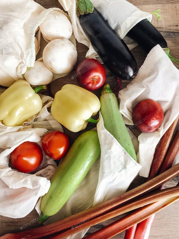 Vegetables in eco cotton bags on table in the kitchen, zero waste shopping