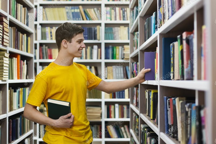 Young caucasian guy taking book from bookshelf