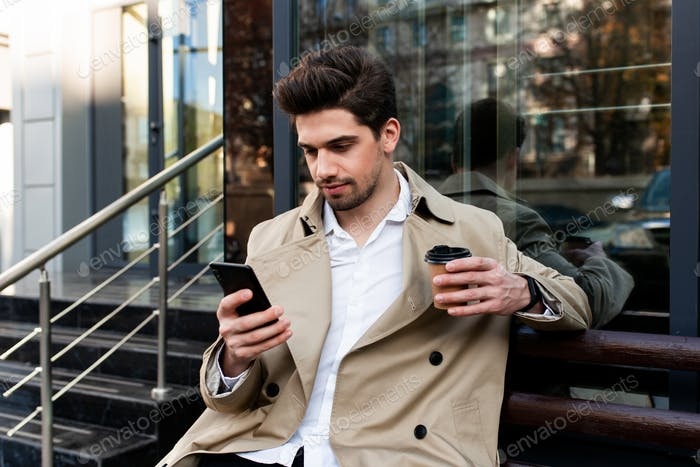 Young handsome casual man in trench coat with coffee to go thoughtfully using cellphone on street
