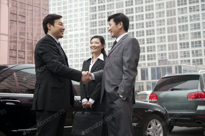 Two businessmen shaking hands next to a car