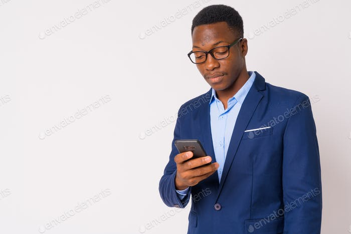 Portrait of young handsome African businessman using phone