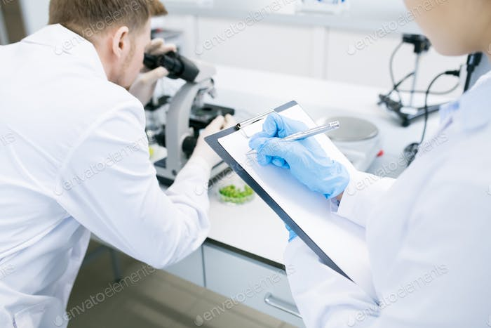 Scientists writing results of research under microscope