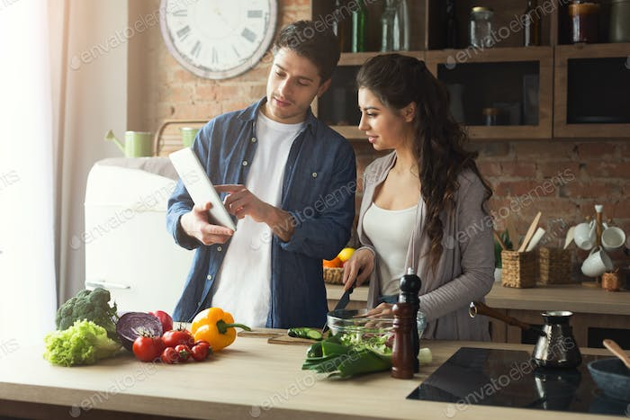 Beautiful young couple reading recipe on tablet