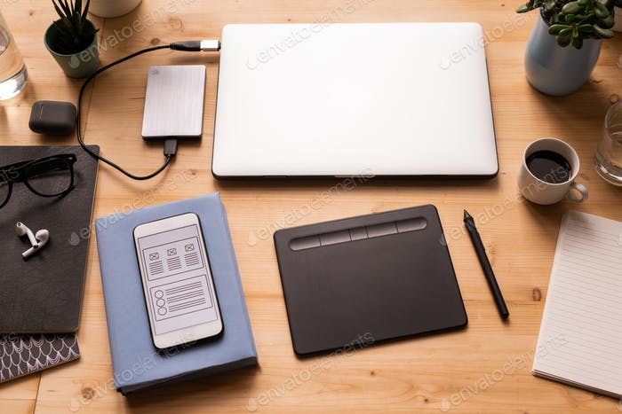 Mobile gadgets, pad with stylus, cup of coffee, notebooks, earphones, etc