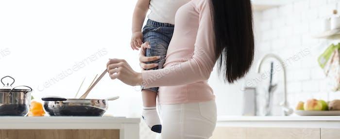 Mutter Kochen mit Säugling auf den Händen, Küche Interieur