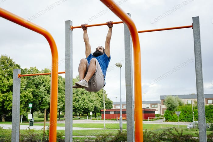 Man exercising on monkey bars