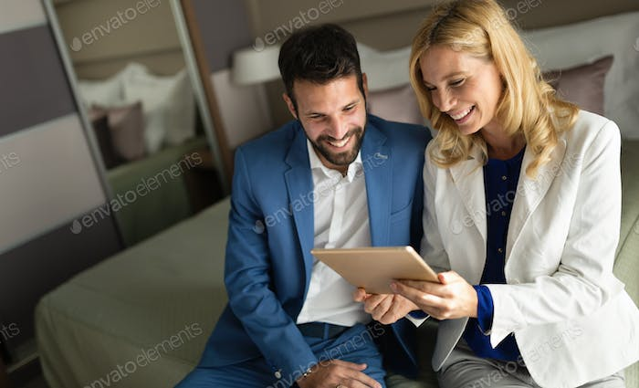 Happy middle aged couple looking at tablet