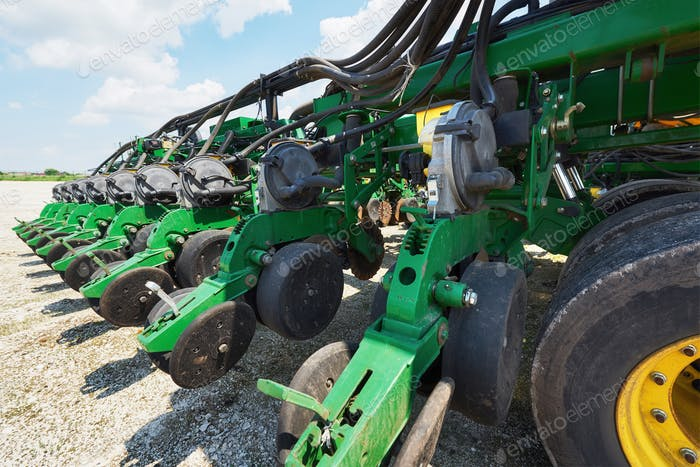 Close up of seeder attached to tractor in field. Agricultural machinery for spring works sowing