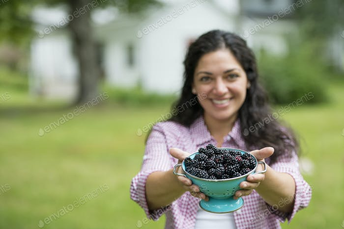 A woman holding a bowl of freshly picked blackberries.