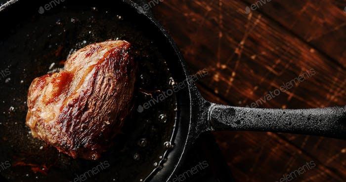 Pfanne mit gebratenem Fleisch auf dem Tisch